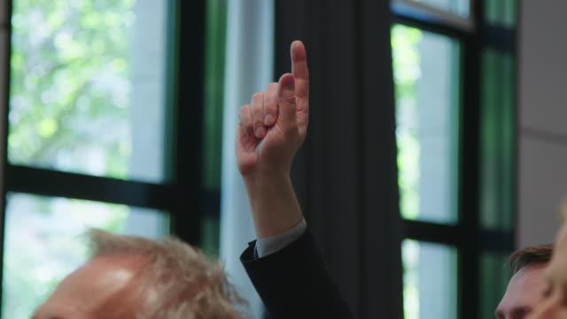 businessman with hand raised in seminar - podnosić filmów i materiałów b-roll