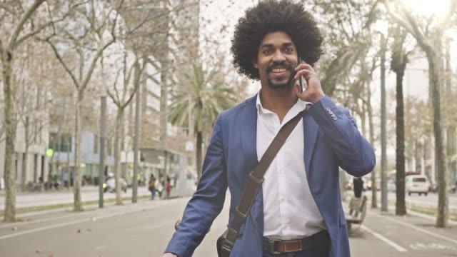 affärsman med sin cykel att ha ett samtal med mobiltelefon i gatan - endast en man i 30 årsåldern bildbanksvideor och videomaterial från bakom kulisserna