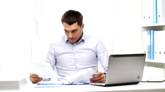 vídeos y material grabado en eventos de stock de hombre de negocios con ordenador portátil y documentos de trabajo en la oficina - gerente de cuentas