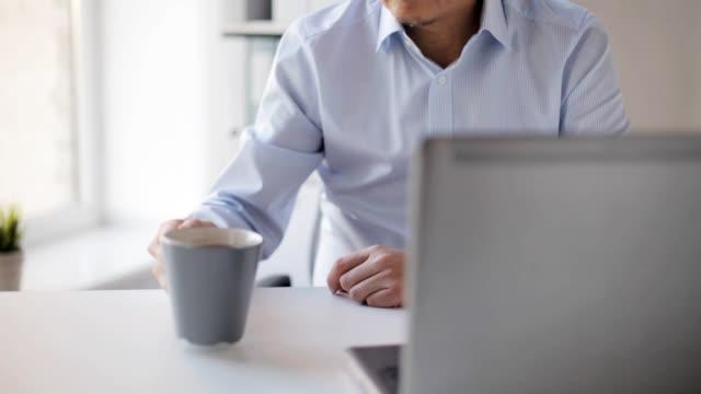 stockvideo's en b-roll-footage met zakenman met laptop drinken koffie op kantoor - {{asset.href}}