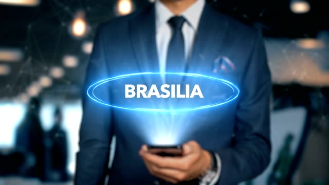 Empresário com telefone móvel abre a Interface de HUD do holograma e toques palavra país - Capital - Brasília - vídeo