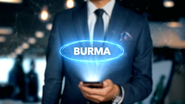 businessman with mobile phone opens hologram hud interface and touches word country - capital - burma - insygnia filmów i materiałów b-roll