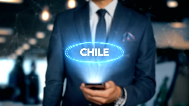 Businessman With Mobile Phone Opens Hologram HUD Interface and Touches Word Country - Capital - CHILE video