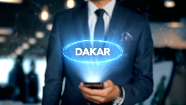 businessman with mobile phone opens hologram hud interface and touches word country - capital - dakar - dakar video stock e b–roll