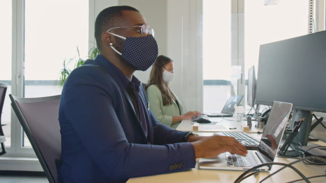 Businessman with protective face mask working at his desk Businessman with protective face mask working at his desk. Business people return back to work after pandemic lockdown sitting at desk with protection guard between them. mask stock videos & royalty-free footage