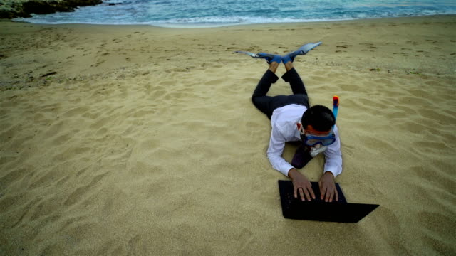 Businessman with snorkel use computer on the beach - 4K video