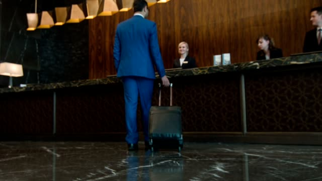 Businessman with suitcase walking to reception desk video