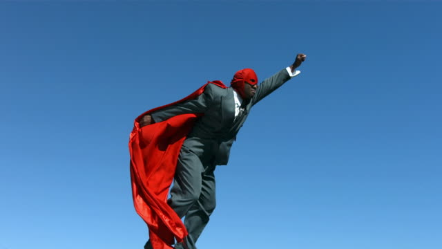 Businessman with superhero mask and cape, slow motion video
