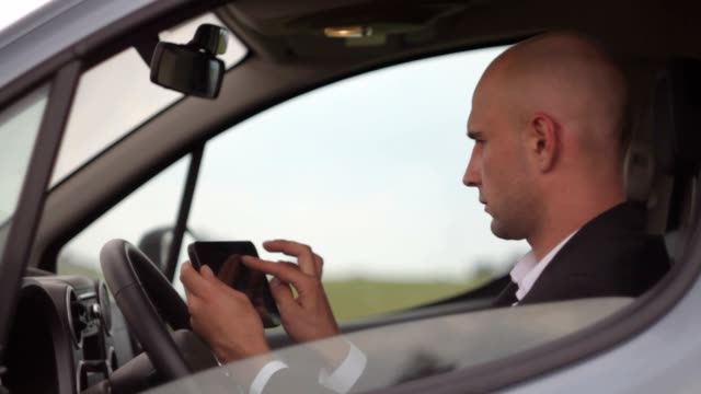 Businessman with tablet in car, traffic jam. video