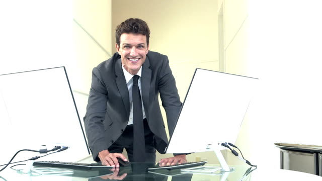 Businessman with two computers A mid adult businessman in a business suit, standing at a table with two desktop computers. He looks at one of the screens, holding a mouse, with a serious expression. Then he looks up at the camera and smiles. leaning stock videos & royalty-free footage