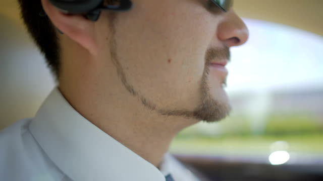 Businessman with well-groomed beard driving car, business trip, meeting video