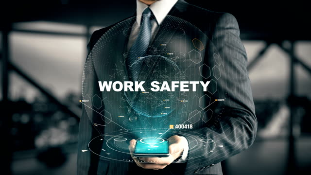 Businessman with Work Safety hologram concept Businessman with hologram in the future with futuristic tablet with success words occupational safety and health stock videos & royalty-free footage