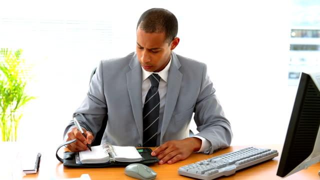 stockvideo's en b-roll-footage met businessman working at his desk and writing in diary - overhemd en stropdas