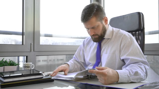 Businessman working, browsing document, data, files, in ring binder in office video