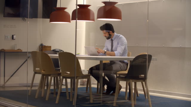 Businessman working in a cubicle at a corporate business video