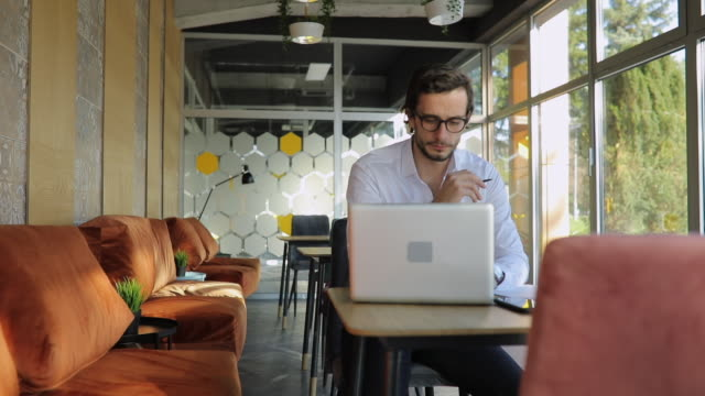 Businessman working in cafe on laptop