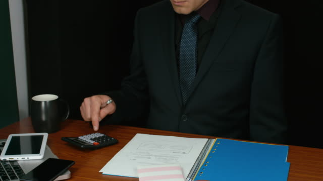 Businessman Working In Office Using A Calculator And Writing video