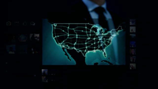 Businessman working on a futuristic holographic interface. Touchscreen. US map.