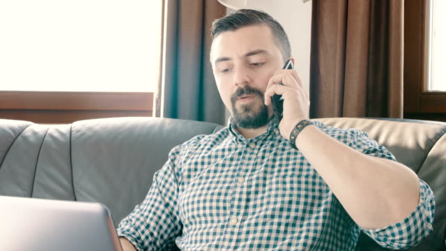 businessman working on a laptop from home and talking on the phone - rispondere video stock e b–roll