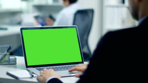 商人與綠色螢幕的筆記本電腦上工作。在背景中他的同事在平板電腦上工作。辦公室是現代和光明。 - laptop 個影片檔及 b 捲影像