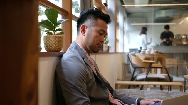 ビジネスマンのカフェで彼のラップトップに取り組んで - ビジネスマン 日本人点の映像素材/bロール
