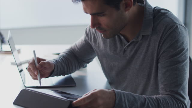 Businessman Working On Laptop At Desk Using Digital Tablet And Stylus