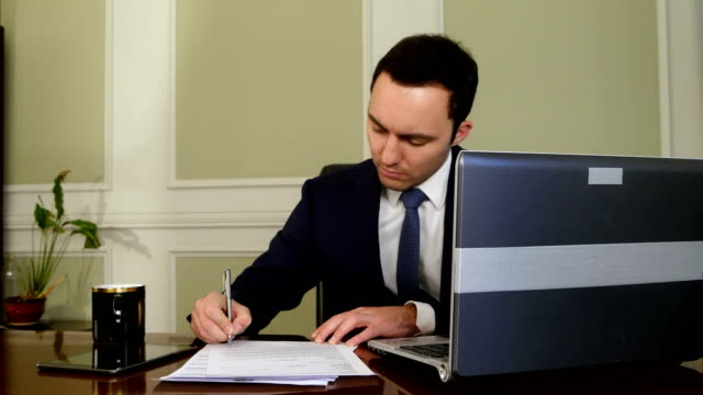 Businessman working on laptop computer in the office video