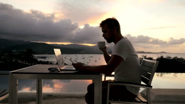 businessman working on notebook on outdoor terrace with view in evening sea - digital mobile consumption video stock e b–roll