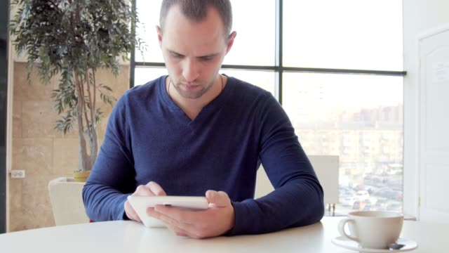 Businessman working on tablet computer and drinking coffee in cafe video