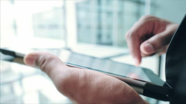 stockvideo's en b-roll-footage met zakenman die aan de tablet werkt. - een tablet gebruiken