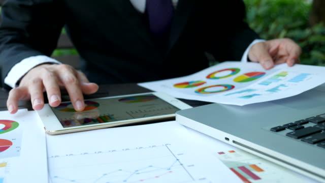 vídeos de stock e filmes b-roll de homem de negócios a trabalhar num o comprimido com os diagramas - risco