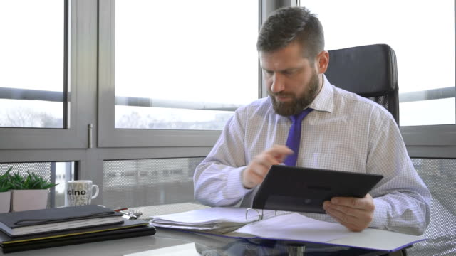 Businessman working with document, data, in ring binder and tablet, office video