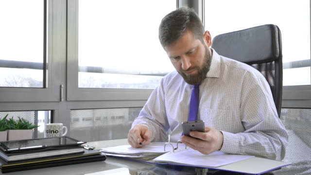 Businessman working with documentin ring binder, looking at camera, office video