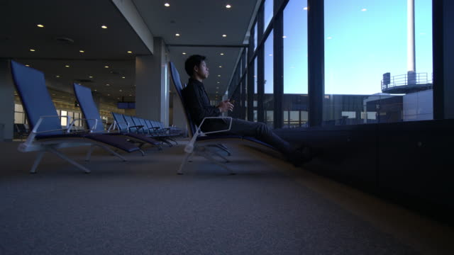 vídeos de stock e filmes b-roll de businessman working with mobile phone at airport - japanese font