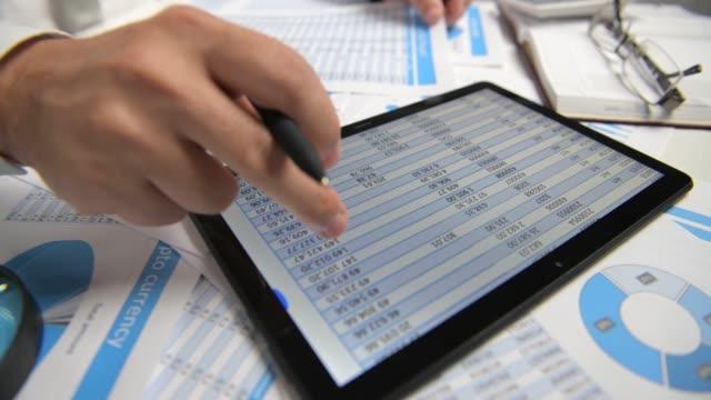 affärs man som arbetar med tablet pc, beräkna, läsa och skriva rapporter. kontors anställd, tabell närbild. affärs redovisning begrepp. - accounting bildbanksvideor och videomaterial från bakom kulisserna