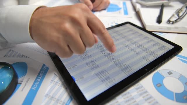 businessman working with tablet pc, calculating, reading and writing reports. office employee, table closeup. business financial accounting concept. - calcolare video stock e b–roll