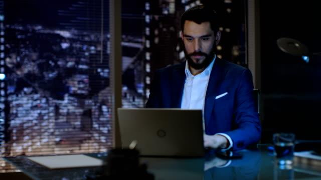 vídeos de stock, filmes e b-roll de homem de negócios funciona em um laptop em seu escritório particular com vista de janela de cidade grande. - países bálticos