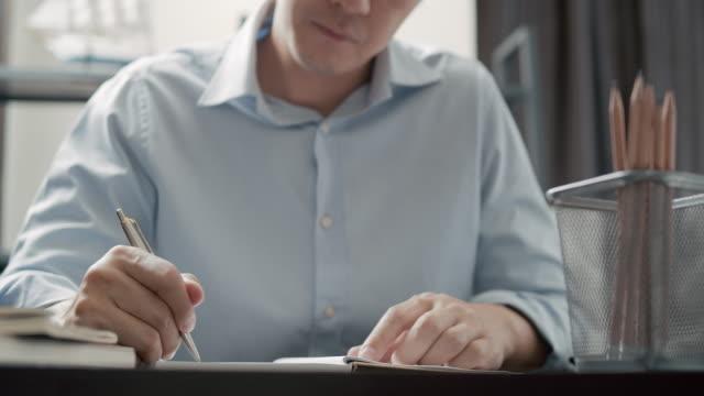vídeos y material grabado en eventos de stock de empresario escribe su plan de negocios en la oficina en casa - planificación financiera