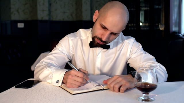 Businessman writing in a notebook sitting in cafe. video