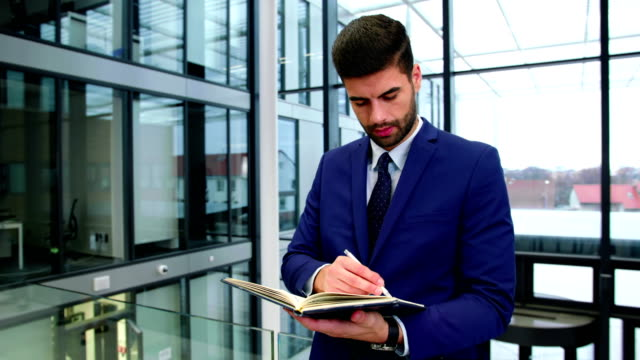 Businessman writing in diary at office video