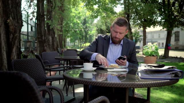 businessman writing on smartphone during lunch. steadicam shot. - scone filmów i materiałów b-roll