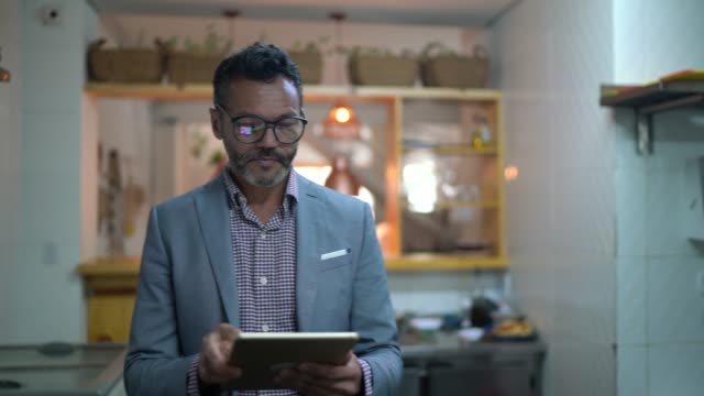 affärsman/ägare använda digital tablet i en restaurang - småföretagande bildbanksvideor och videomaterial från bakom kulisserna