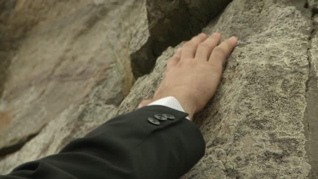 Businessman's hand reaches for grip.