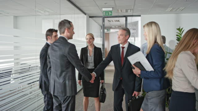 businessmen and a businesswoman shaking hands before entering the meeting room with a female assistant - business handshake stock videos & royalty-free footage