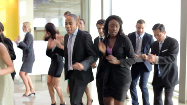 Businessmen And Businesswomen Dancing In Office Lobby Female boss standing and talking to group of colleagues seated at boardroom table.Shot on Sony FS700 in PAL format at a frame rate of 25fps group of objects stock videos & royalty-free footage