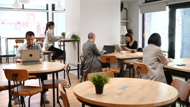 Businessmen and woman working in open plan office coworking space Freelance workers sitting at tables and using laptops, focus, efficiency, technology coworking stock videos & royalty-free footage