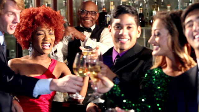 Businessmen and women with drinks at bar toasting video