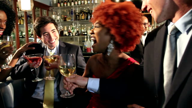 Businessmen and women with drinks at bar video