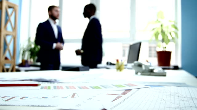 Businessmen conduct business. Focus on documentation. The camera moves from right to left video