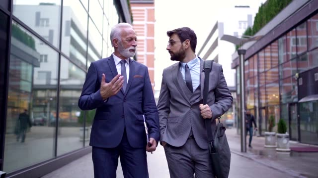 businessmen have a conversation on the way to work - fianco a fianco video stock e b–roll